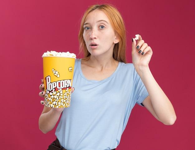 Ragazza ansiosa dello zenzero giovane rossa con le lentiggini che tengono il secchio del popcorn sul colore rosa