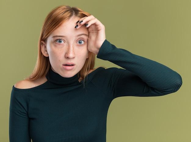 주근깨가 있는 불안한 어린 빨간 머리 생강 소녀는 복사 공간이 있는 올리브 녹색 벽에 격리된 이마에 손을 얹습니다