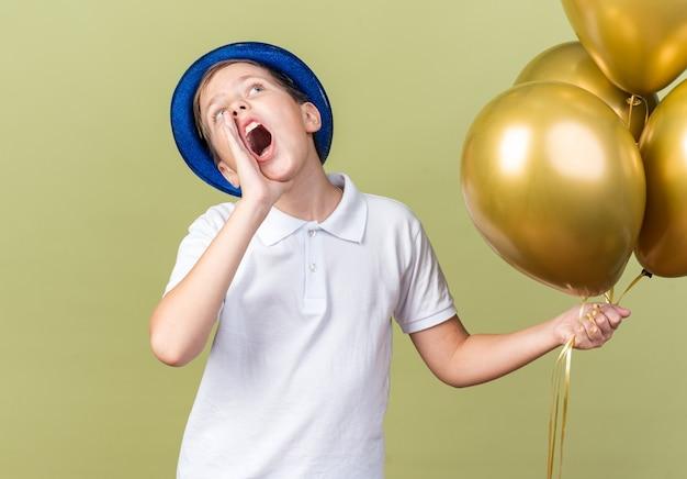 ヘリウム気球を保持し、コピースペースでオリーブグリーンの壁に孤立して見上げる誰かを呼び出す口の近くに手を保つ青いパーティーハットを持つ気になる若いスラブ少年