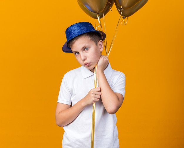 Anxious young slavic boy with blue party hat holding helium balloons isolated on orange wall with copy space