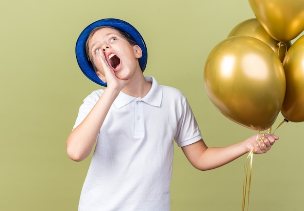 Anxious young slavic boy with blue party hat holding helium balloons and keeping hand close to mouth calling someone looking up isolated on olive green wall with copy space