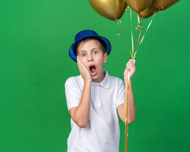 Anxious young slavic boy with blue party hat putting hand on face and holding helium balloons isolated on green wall with copy space