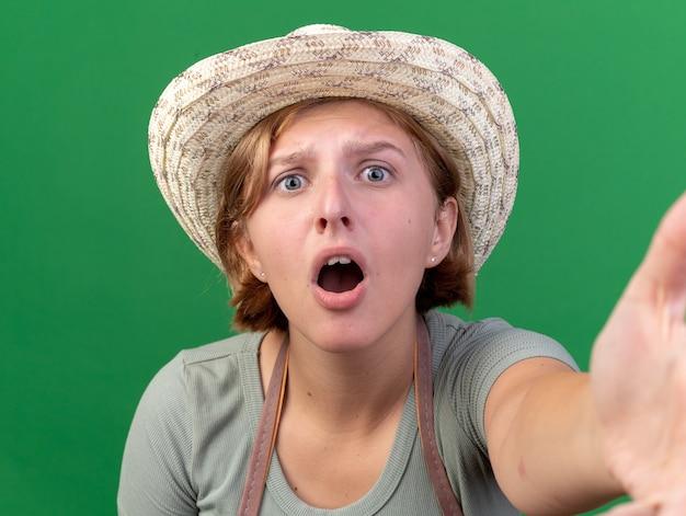 緑にカメラを保持するふりをしてカメラを見てガーデニング帽子をかぶって気になる若いスラブ女性の庭師