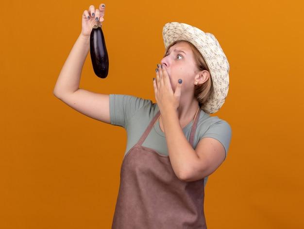 Ansioso giovane giardiniere femmina slava che indossa un cappello da giardinaggio mette la mano sulla bocca tenendo e guardando la melanzana