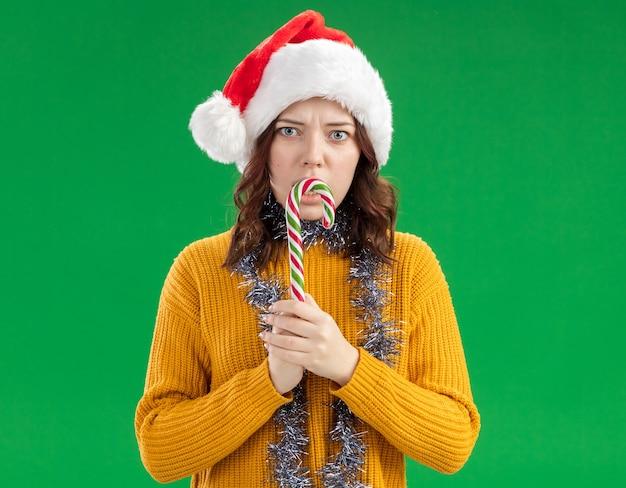 Взволнованная молодая славянская девушка в новогодней шапке и с гирляндой на шее держит конфету, изолированную на зеленом фоне с копией пространства