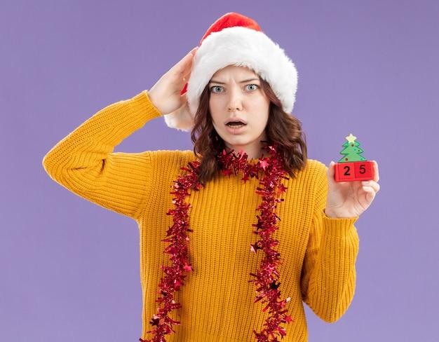 サンタの帽子と首に花輪を持つ気になる若いスラブの女の子は頭に手を置き、コピースペースで紫色の背景に分離されたクリスマスツリーの飾りを保持します。