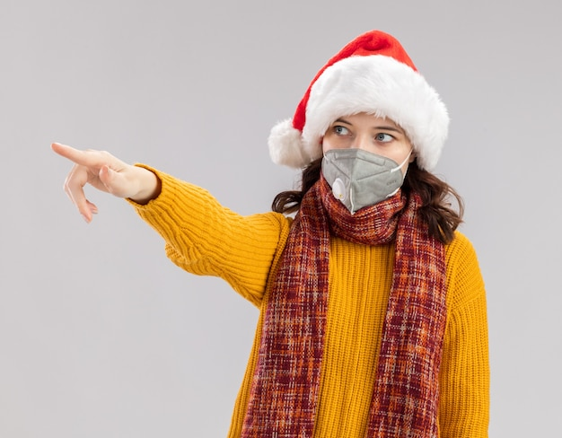サンタの帽子と首の周りのスカーフと医療マスクを身に着けている不安な若いスラブの女の子は、コピースペースで白い背景で隔離された側を見て、指しています