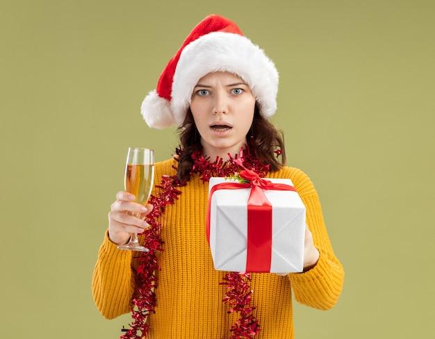 Ansiosa giovane ragazza slava con cappello da babbo natale e con ghirlanda intorno al collo con in mano un bicchiere di champagne e una confezione regalo di natale isolata sulla parete verde oliva con spazio di copia