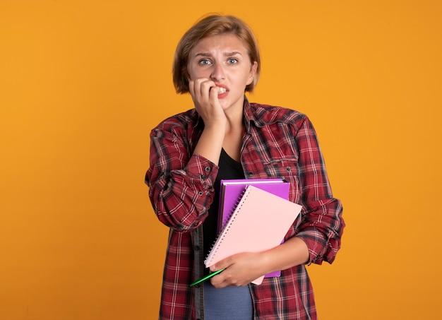 気になる若いスラブ学生の女の子が本とノートを保持している爪をかむ
