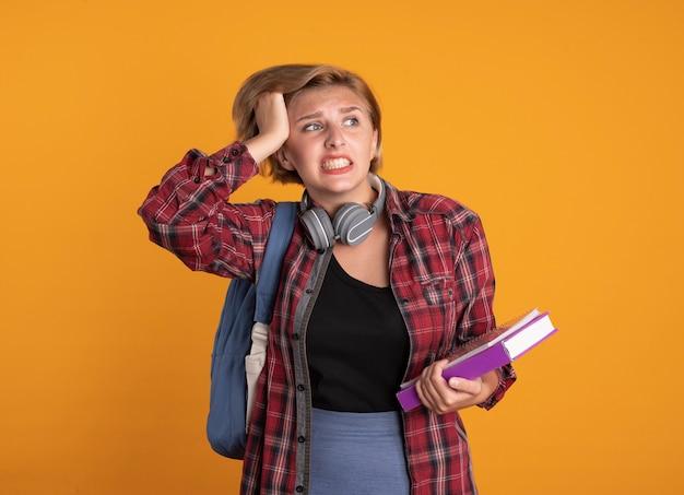 Ansiosa giovane studentessa slava con le cuffie che indossa lo zaino mette la mano sulla testa tiene libro e taccuino