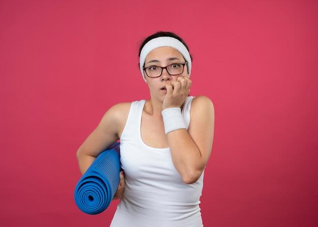 Ansiosa giovane donna sportiva in occhiali ottici che indossa la fascia e braccialetti morde le unghie e tiene il tappetino sportivo isolato sul muro rosa