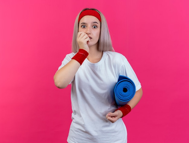 Ansiosa giovane donna sportiva con bretelle che indossano fascia e braccialetti morde le unghie e tiene il tappetino sportivo isolato sul muro rosa