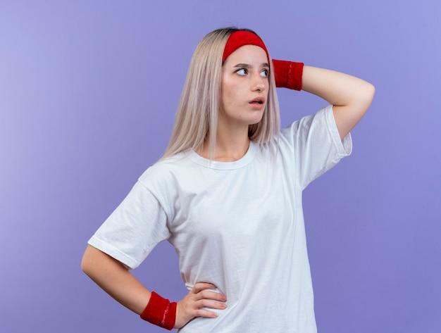 Ansiosa giovane donna sportiva con bretelle che indossa fascia e braccialetti mette la mano sulla testa e guarda il lato isolato sul muro viola