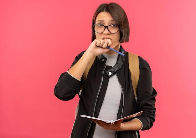 コピースペースでピンクで隔離された口の近くで手を保つメモ帳とペンを保持している眼鏡とバックバッグを身に着けている気になる若い学生の女の子