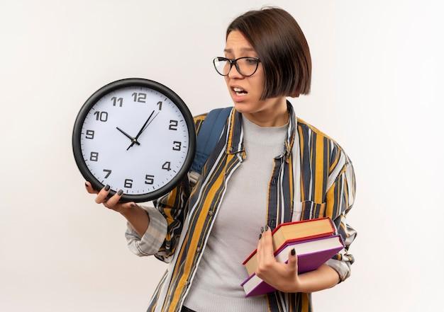 Ansioso giovane studente ragazza con gli occhiali e borsa posteriore in possesso di libri e orologio guardando l'orologio isolato su bianco