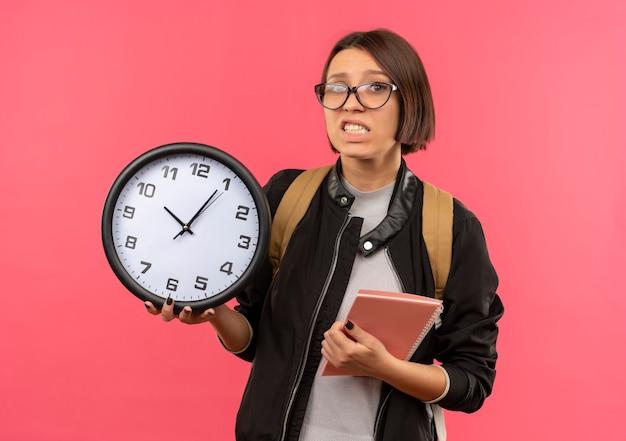 Ansioso giovane studente ragazza con gli occhiali e borsa posteriore che tiene orologio e blocco note isolato sul rosa
