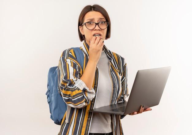 Ansioso giovane studente ragazza con gli occhiali e borsa posteriore tenendo il computer portatile mettendo la mano sul mento isolato su bianco con copia spazio