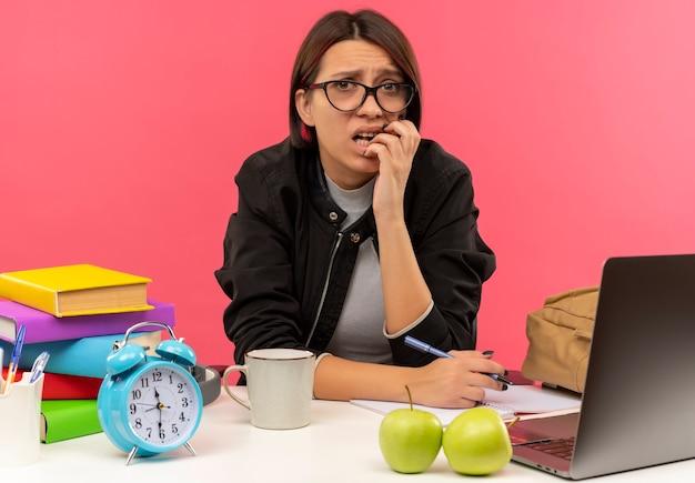 Ansioso giovane studente ragazza con gli occhiali seduto alla scrivania a fare i compiti mettendo la mano sulle labbra tenendo la penna isolata sul rosa