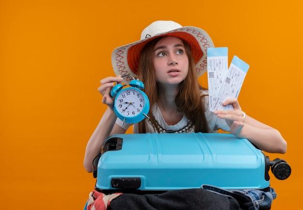 Взволнованная молодая путешественница держит билеты на самолет и будильник с чемоданом на изолированном оранжевом пространстве с копией пространства
