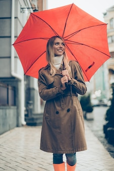 Any weather is good. attractive young smiling woman in colorful rubber boots carrying umbrella and looking away while walking by the street
