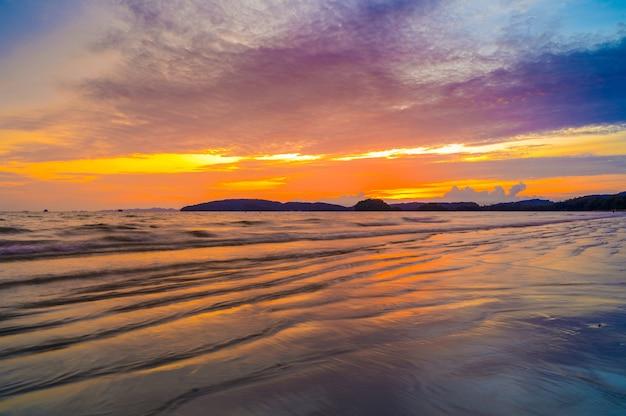 Ao nang krabi thailand на пляже много людей по вечерам. золотой свет