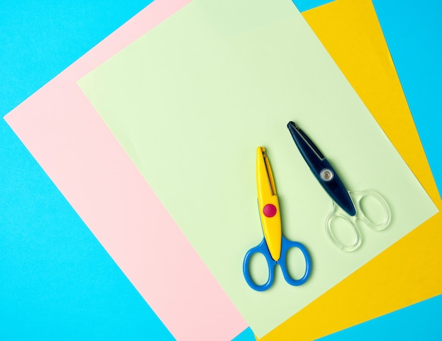 Apair of plastic scissors and colored paper on a blue background