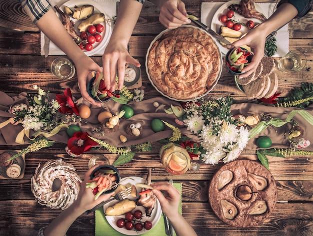 Квартира-праздник друзей или семьи за праздничным столом с мясом кролика, овощами, пирогами, яйцами, видом сверху.