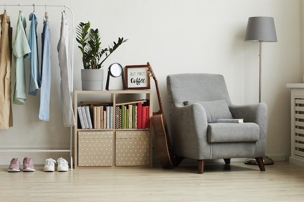 Apartment interior with minimal design, focus on comfy grey armchair and clothes rack against white wall