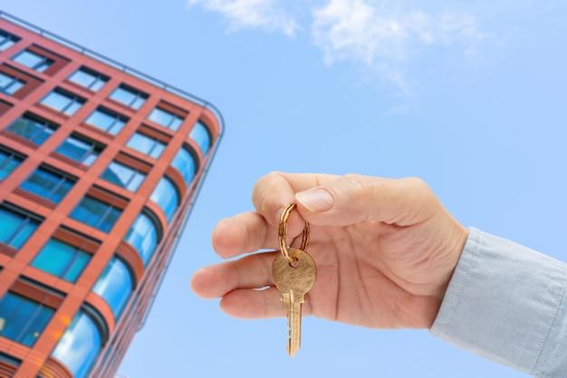男の手にあるアパートの鍵。真ちゅう製の家のドアロックキー。モダンな建物、下からの眺め。近代都市の建築。不動産の販売および賃貸。