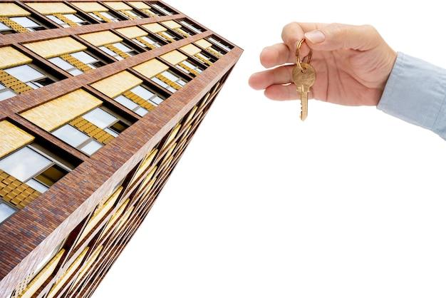 남자의 손에 아파트 키입니다. 황동 집 도어 잠금 키입니다. 현대적인 건물, 아래에서 볼 수 있습니다. 현대 도시의 건축. 부동산 판매 및 임대.