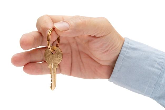 Ключ от квартиры в мужской руке. ключ от латунного замка двери дома.