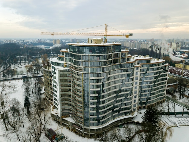 Apartment or office building under construction, aerial view. tower crane silhouette on blue sky copy space background.
