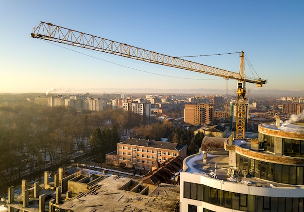 Apartment or office tall building under construction, top view. tower crane on bright blue sky copy space, city landscape stretching to horizon. drone aerial photography.