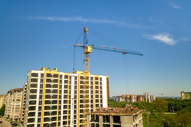 Apartment or office tall building under construction. working builders and tower cranes on bright blue sky copy.