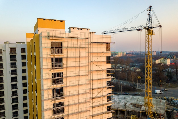 Apartment or office tall unfinished building under construction. brick wall in scaffolding, shiny windows and tower crane on urban landscape and blue sky. drone aerial photography.