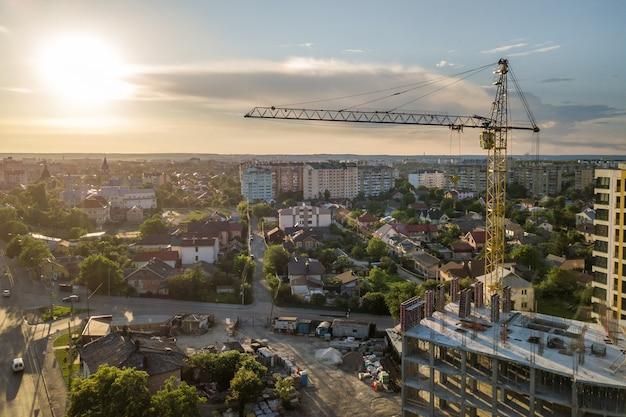 아파트 또는 사무실 고층 빌딩 건설 중입니다. 벽돌 벽, 유리창, 비계 및 콘크리트지지 기둥. 밝은 푸른 하늘 복사 공간에 타워 크레인