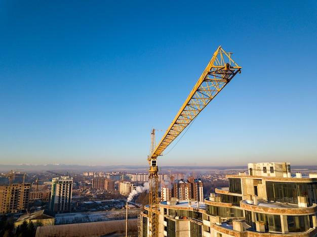 建設中のアパートまたはオフィスの高層ビル、平面図。明るい青空コピースペース背景、地平線に伸びる都市景観のタワークレーン。ドローン航空写真。