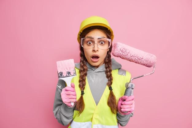 マンションリノベーションのコンセプト。ショックを受けた多忙な女性保守労働者は保護用のヘルメット メガネを着用し、ユニフォームは家の再建に建築設備を使用し、驚くべきことに反応する