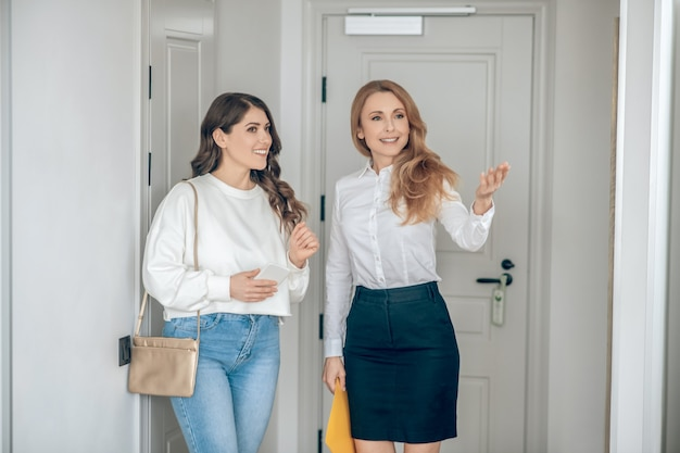 아파트 임대료. 여성 고객에게 아파트를 보여주는 부동산 중개인