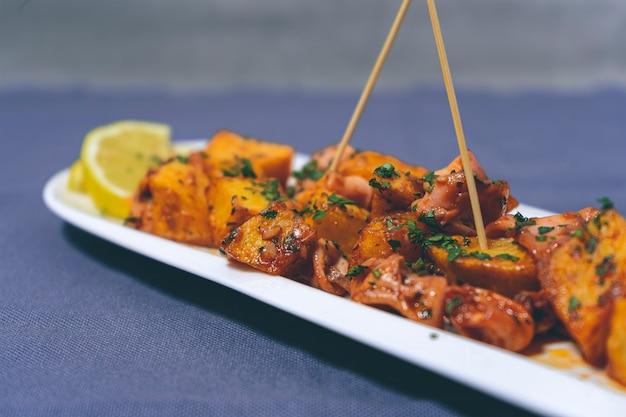 食前酒または典型的なスペインのタパスベビーイカにニンニクとジャガイモを添えて、細長い白で提供
