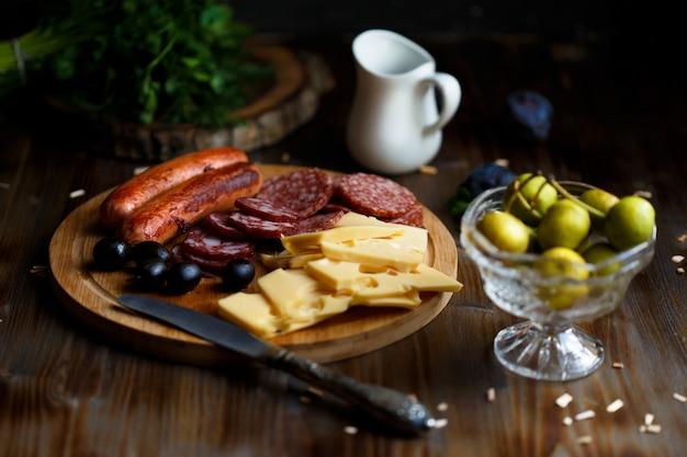 Аперитив столовый мясная закуска, жареные колбаски, сыр, салями, оливки и бокал вина на темном столе