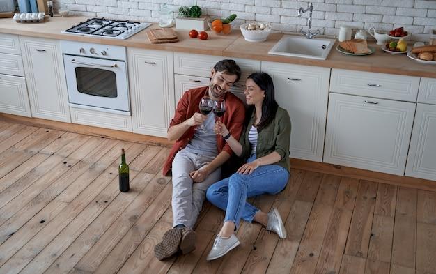 モダンなキッチンの床に座っている若い美しいカップルの食前酒の時間の全長