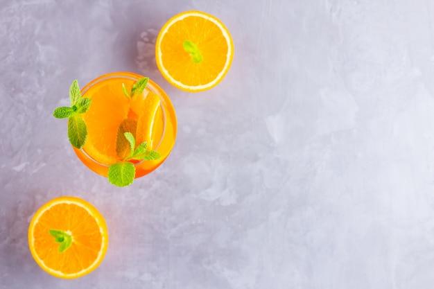 灰色の背景にaperolスプリッツカクテル。オレンジ色のスライスされたaperol spritzのガラス。上面図。