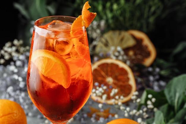 Коктейль aperol spritz на сером бетонном столе. стакан aperol spritz с дольками апельсина. летний коктейль в бокале