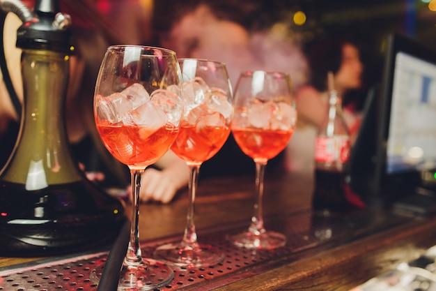 Aperol spritz коктейль. алкогольный напиток на основе таблицы с кубиками льда и апельсинами.