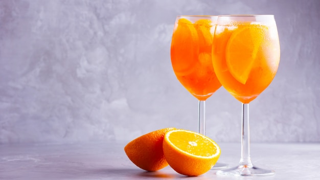 Aperol spritz cocktail on a gray table. two glasses of aperol spritz