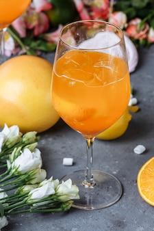 Коктейль aperol spritz в большом стакане, летний итальянский слабоалкогольный холодный напиток. на декоративном фоне, с клубникой, апельсином и декором.