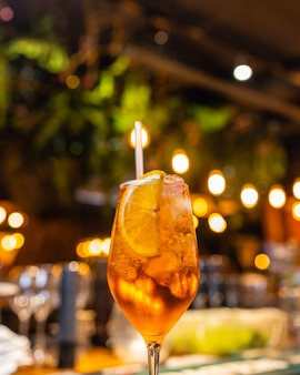 カフェの暗い背景の上の木製のテーブルにガラスのアペロールスプリッツカクテル。