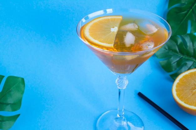 Коктейль aperol spritz в бокале мартини на тропическом фоне. скопируйте пространство. крупный план.