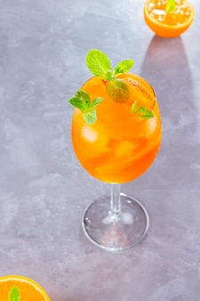 Aperol spritz коктейль на сером фоне. стекло aperol spritz с апельсиновой нарезкой. вид сверху.